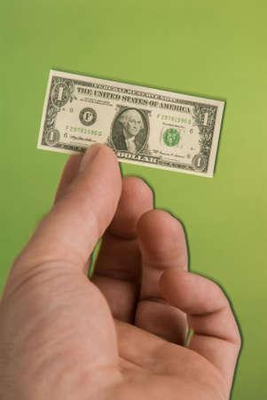 unequal: una parte la celebraci�n de una miniatura de un d�lar de Estados Unidos proyecto de ley que representa la disminuci�n de d�lar de los Estados Unidos Foto de archivo