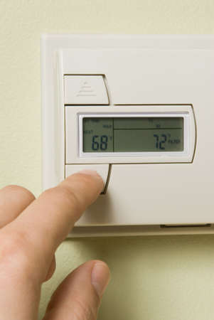 adjusting a home thermostat to save energy
