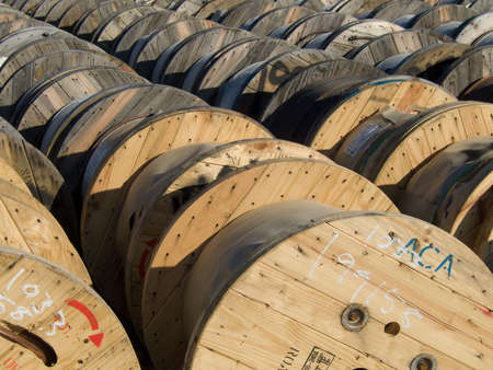 wooden spools of wire in the yard of a power company utility