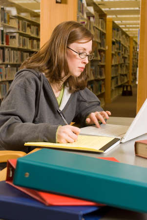 dissertation: a young woman studies in the library Stock Photo