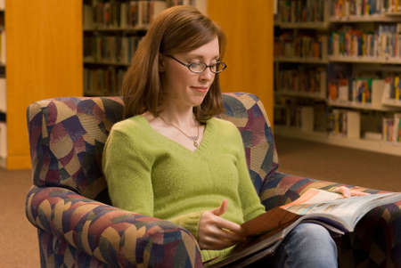 aisles: a young woman sitting in a chair at the library reading a magazine
