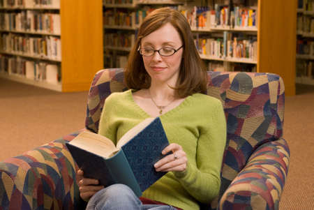 aisles: a young woman sitting in a chair at the library reading a book