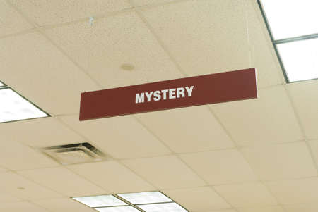 a sign hanging from a library ceiling indicates the mystery section Imagens
