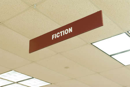 a sign hanging from a library ceiling indicates the fiction section Banco de Imagens