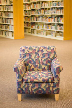 aisles: a reading chair in a library with book stacks in the background