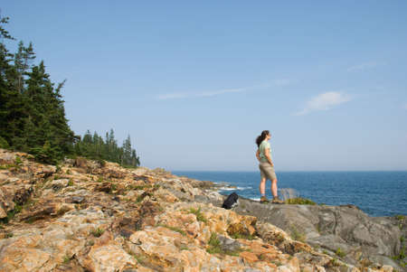a woman stands on the rocky coastline of Maine.  Acadia National Park