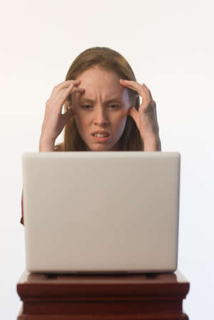 dismay: An angry confused young woman looking at her laptop screen Stock Photo