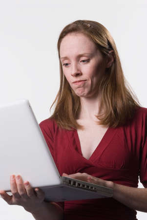 a young woman looks down at her laptop computer screen with a disconcerted look on her face Stok Fotoğraf