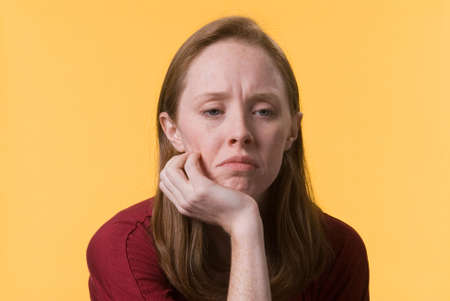 a sad depressed young woman with her hand on her chin Stock Photo - 6704689