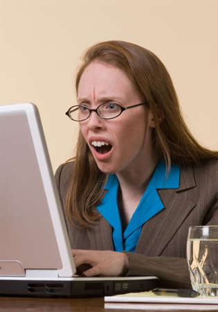 disbelief: a young  business woman gasps in disbelief at her laptop computer screen