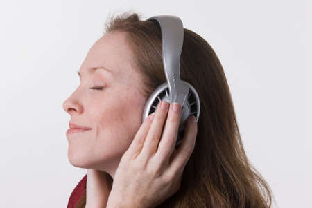 a young woman joyfully listens to music on headphone while her hands hold the earpieces photo