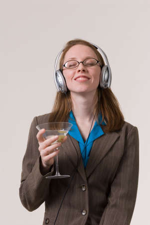 a young business woman relaxes with a martini and music after work photo
