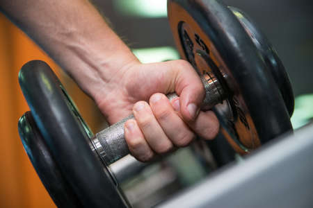 lift hands: Close-up image of male hand holding dumbbell Stock Photo