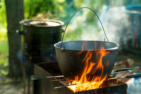 Cooking in sooty bowler on campfire at forest during hike Stock Photo