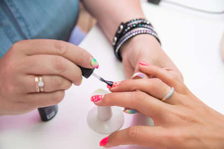 vouge: Woman in salon receiving manicure by nail beautician