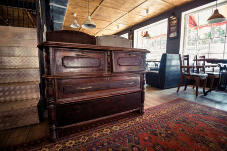 highboy: Old vintage wooden chest of drawers in pub interior Stock Photo