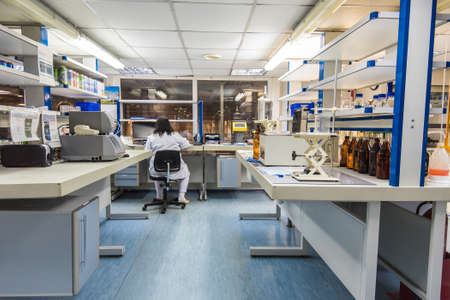 Interior of modern research laboratory and woman scientist