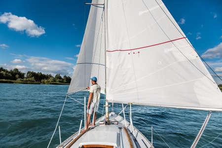 yachtsman: Yachtsman controls his sailing boat during voyage