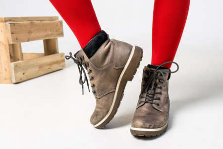 Detail of standing woman wearing fashionable brown boots posing on white Stock Photo