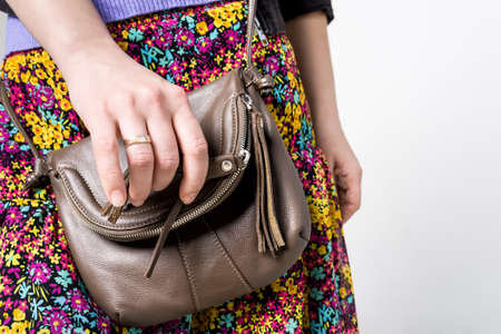 vouge: Closeup of attractive young woman wearing jeans and leather brown handbag on white background