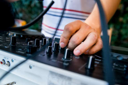 remix: Close-up image of mixing console and DJs hands during his job at party
