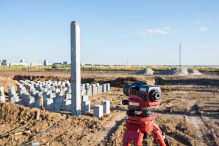 teodolito: Teodolito en frente del campo de las pilas en el emplazamiento de la obra Foto de archivo
