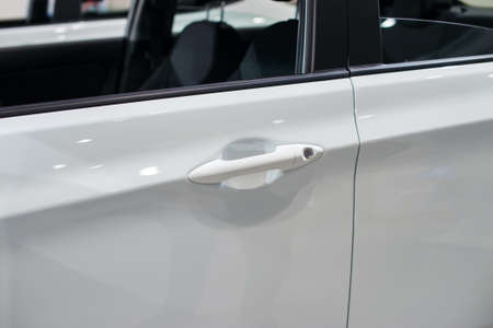 land locked: Close-up photograph of doorknob of a white car