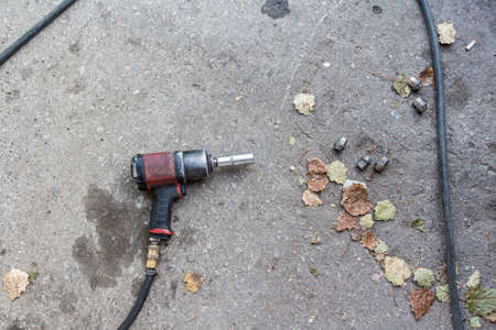 Image of used old pneumatic wrench on ground Stock Photo