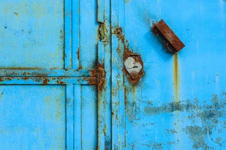 Old rusty metal door painted blue Stock Photo