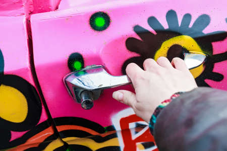 Girl hand holding doorhandle of pink colorful car Stock Photo
