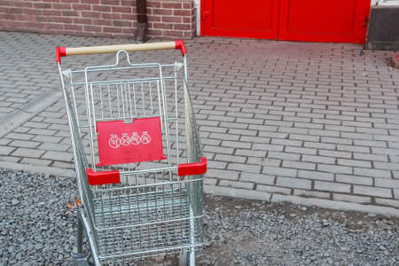 impersonal: Close up of red shopping cart outside supermarket
