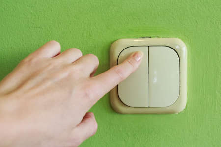 Female hand pressing two keys beige light switch mounted on green wall Stock Photo