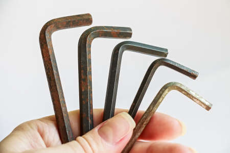 Hand holds set of used rusty hex keys