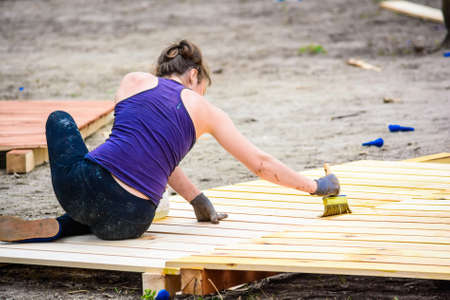 handywoman: Young woman applies varnish on wooden planks Stock Photo