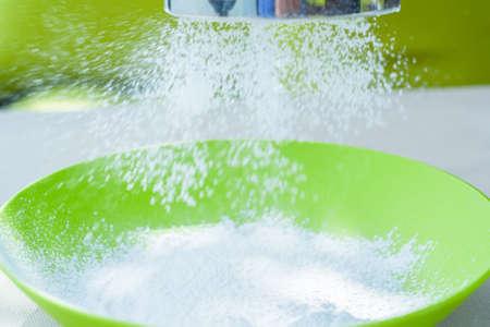Sifting sugar powder in green bowl Stock Photo