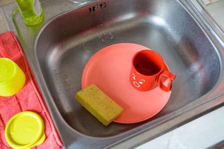 lavar platos: Platos de plástico brillante en el fregadero con esponja