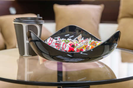 Modern black bowl full of sweets and coffee cup Stock Photo