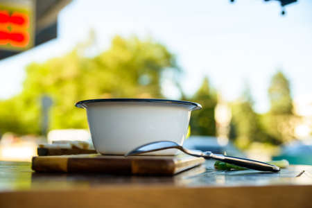 mustard leaf: Metal bowl with soup on wooden table outdoors Stock Photo