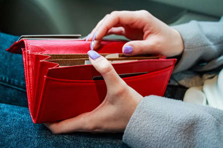 Female hands hold modern red money purse for women
