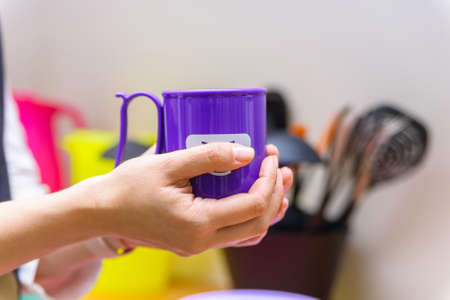 Hands hold plastic cup with smiling face