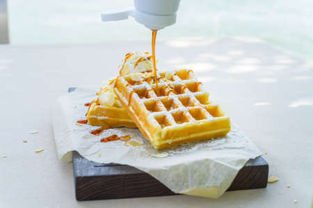 Caramel syrup put on belgian waffles Stock Photo