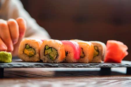 Eating sushi rainbow roll in restaurant