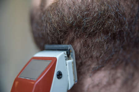Close up young man shaving with electric razor