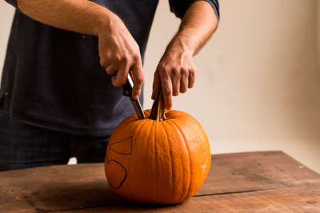 Close up man carves pumpkin with a knife for Halloween
