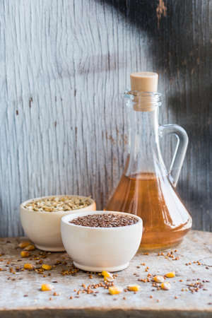 linum: Close up bowl with linseed and decanter of oil Stock Photo