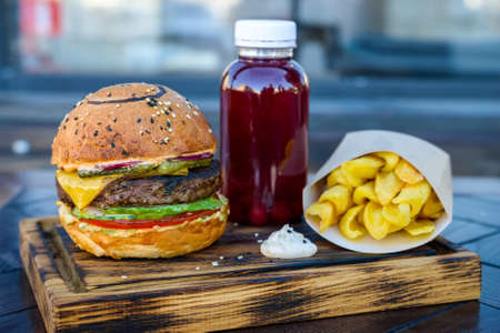 Close up delicious burger and potato wedges and plastic bottle of red juice on wooden board in restaurant Stock Photo