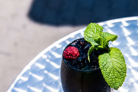 Dark restaurant cocktail with mint and raspberry