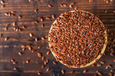 Ciérrese encima de la linaza en cuenco de madera en la tabla de madera