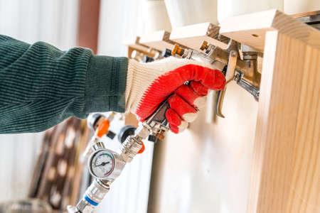 Hand takes spray gun in woodworking workshop