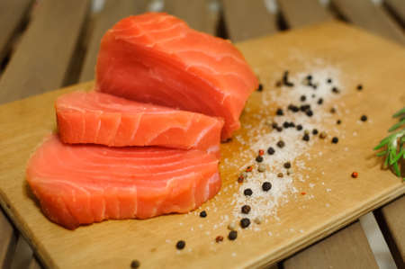 Sliced salmon fillet and pepper on cutting board Stock Photo